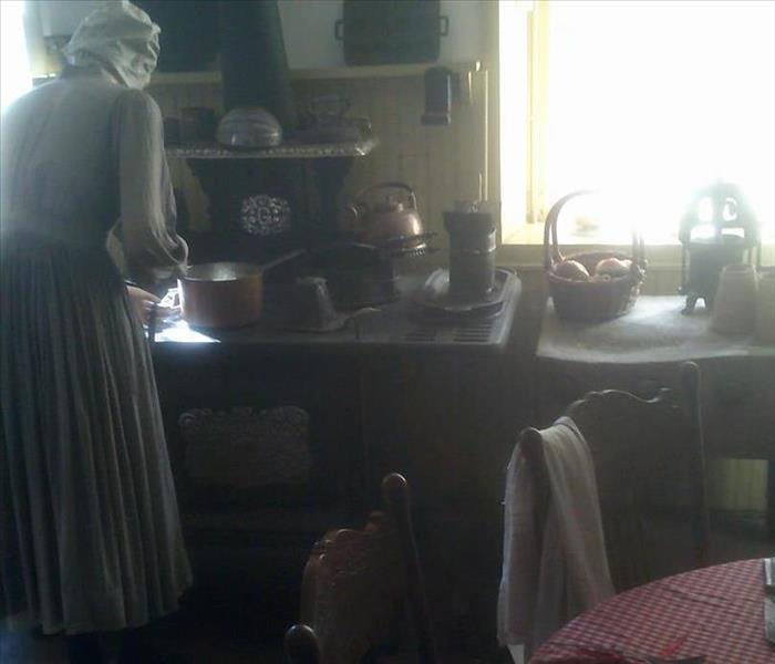 Historic kitchn replicated to include old world kitchen set up with containers, sink & manequin dressed in period time dress