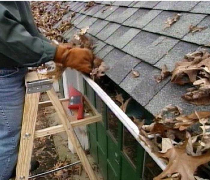 Homeowner is cleaning leaves, dirt & sticks out of his gutters to help prevent storm damage throughout the winter.